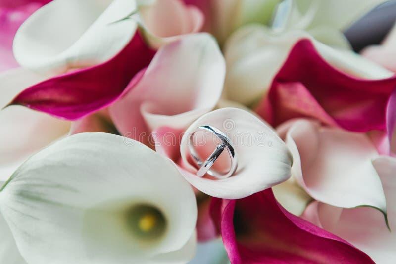 Sistema de anillos de bodas en flores rosadas y blancas foto de archivo libre de regalías
