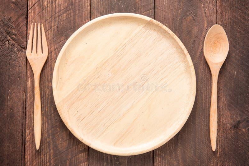 Sistema de bifurcación, de cuchara y de madera del plato en la tabla de madera fotografía de archivo libre de regalías