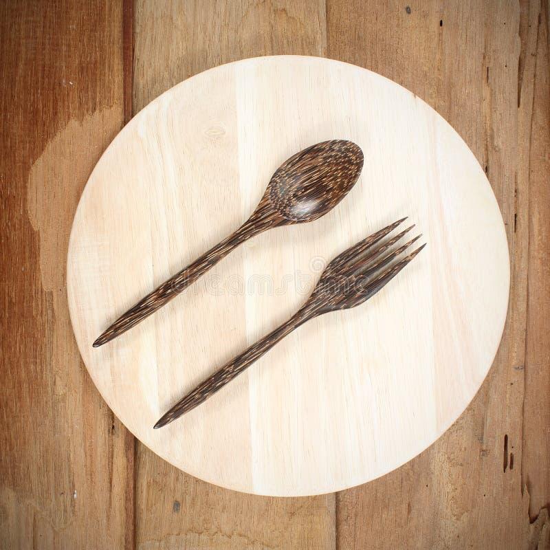 Sistema de bifurcación, de cuchara y de madera del plato en la tabla de madera fotos de archivo libres de regalías