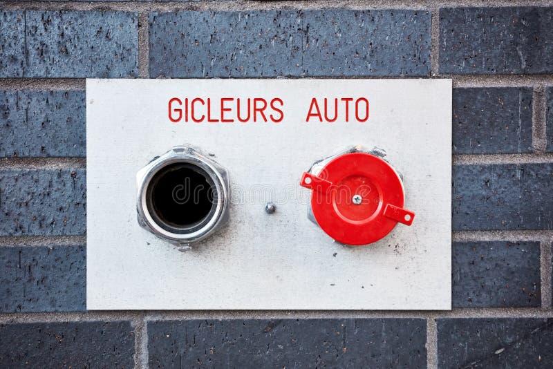 Sistema de boca de incêndio do fogo dos auto gicleurs do sistema de extinção de incêndios auto em uma parede de tijolo imagem de stock