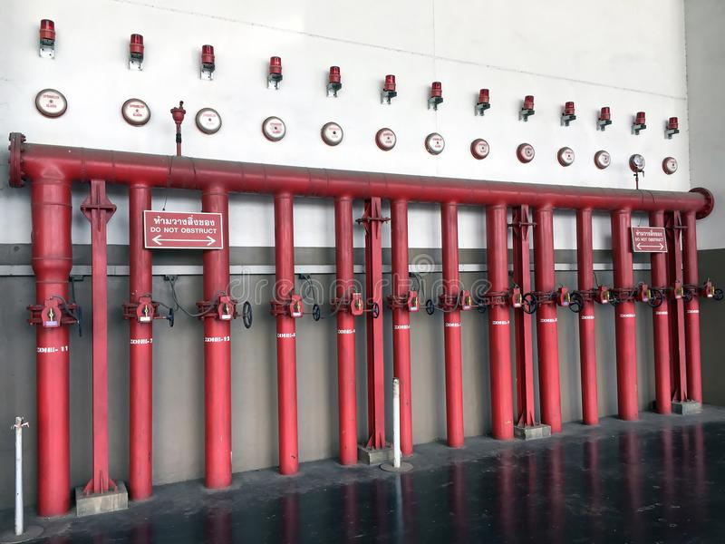 Sistema de boca de incendios integrado por el tubo rojo del fuego del hierro, el interruptor para el agua, la alarma de la regade fotografía de archivo libre de regalías