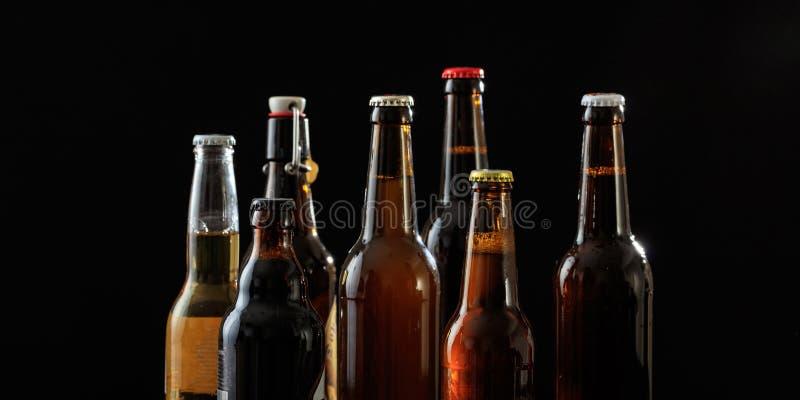 Sistema de botellas de cerveza en fondo negro fotos de archivo