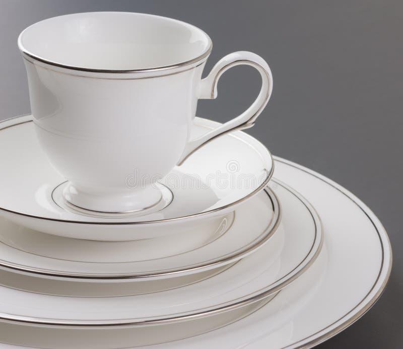 Sistema de cena del blanco hermoso, del borde del oro y de la taza. fotos de archivo