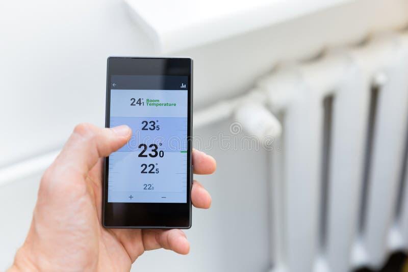 Sistema de controlo da temperatura de aquecimento da casa com telefone esperto imagem de stock royalty free