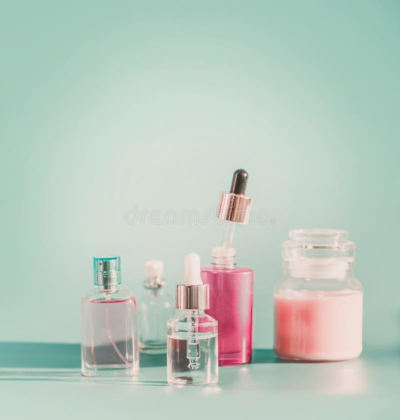 Sistema de cosméticos faciales modernos del cuidado de piel en las botellas azules del producto del fondo foto de archivo
