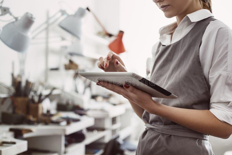 Sistema de CRM O gerente de produção fêmea principal que trabalha em linha com sua tabuleta digital fotografia de stock royalty free