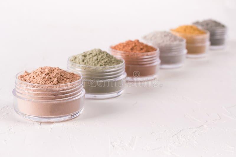 Sistema de diversos polvos cosméticos del fango de la arcilla en blanco foto de archivo