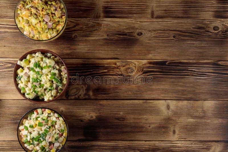 Sistema de ensaladas festivas de la mayonesa en la tabla de madera Visión superior foto de archivo