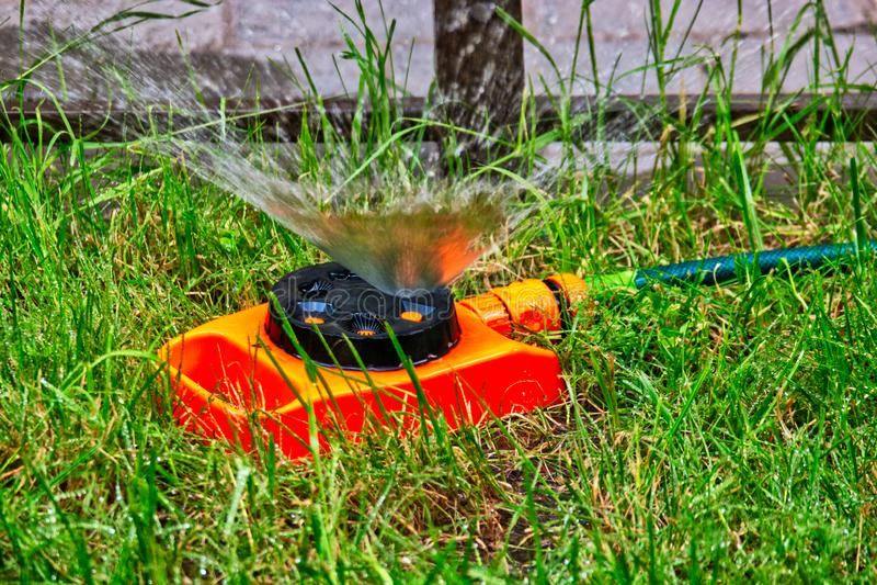Sistema de extinção de incêndios do jardim da cor alaranjada que trabalha no gramado com a fonte da água em um ar imagem de stock