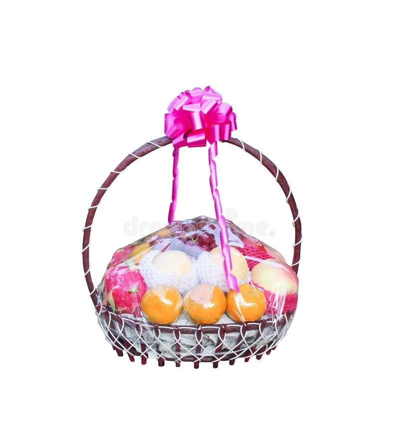 Sistema de frutas multicoloras en el regalo de madera de la cesta con la cinta rosada colorida de la flor aislada en el fondo bla imagenes de archivo
