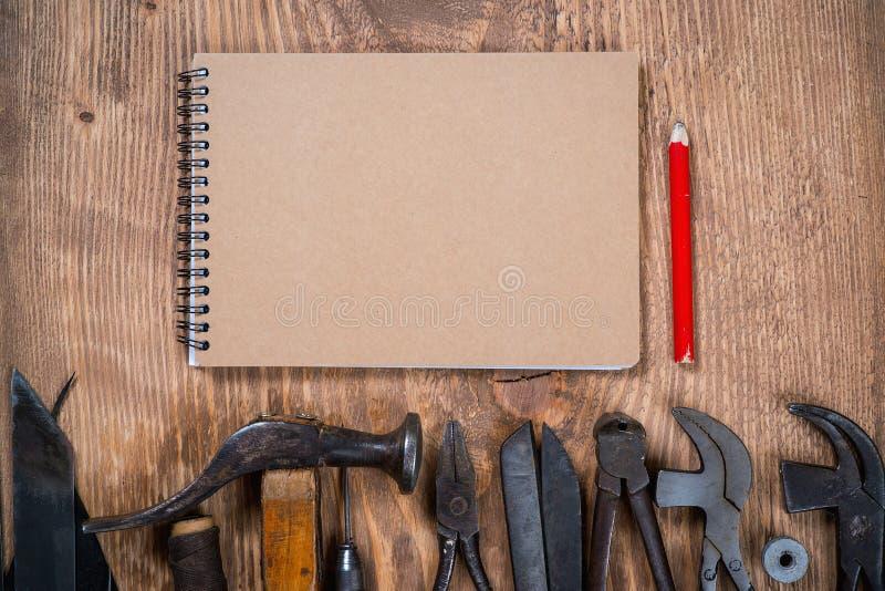 Sistema de herramientas, cuaderno, lápiz para el zapatero en un fondo de madera fotos de archivo