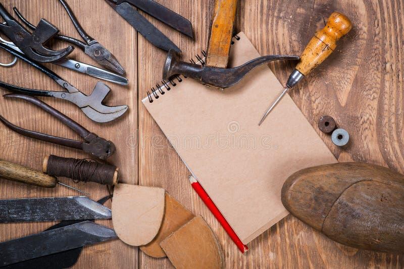 Sistema de herramientas, cuaderno, lápiz para el zapatero en un fondo de madera fotografía de archivo