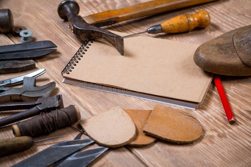 Sistema de herramientas, cuaderno, lápiz para el zapatero en un fondo de madera imagen de archivo