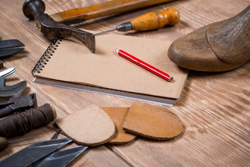 Sistema de herramientas, cuaderno, lápiz para el zapatero en un fondo de madera fotografía de archivo libre de regalías