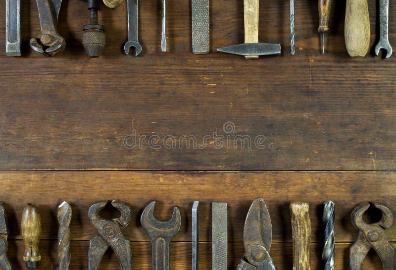 Sistema de herramientas oxidadas viejas en fondo de madera rústico fotografía de archivo