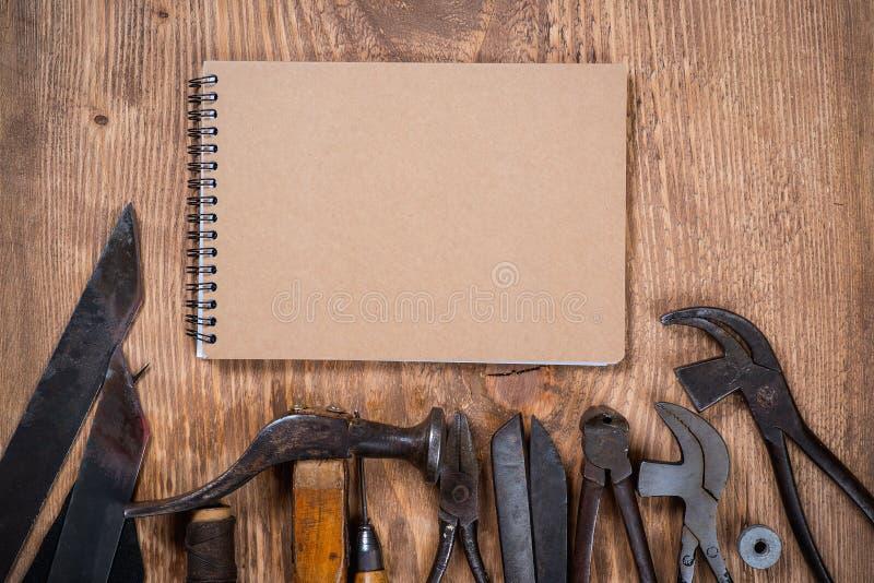 Sistema de herramientas y del cuaderno para el zapatero en un fondo de madera foto de archivo