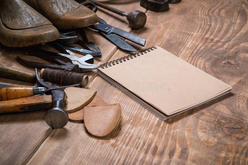 Sistema de herramientas y del cuaderno para el zapatero en un fondo de madera foto de archivo libre de regalías