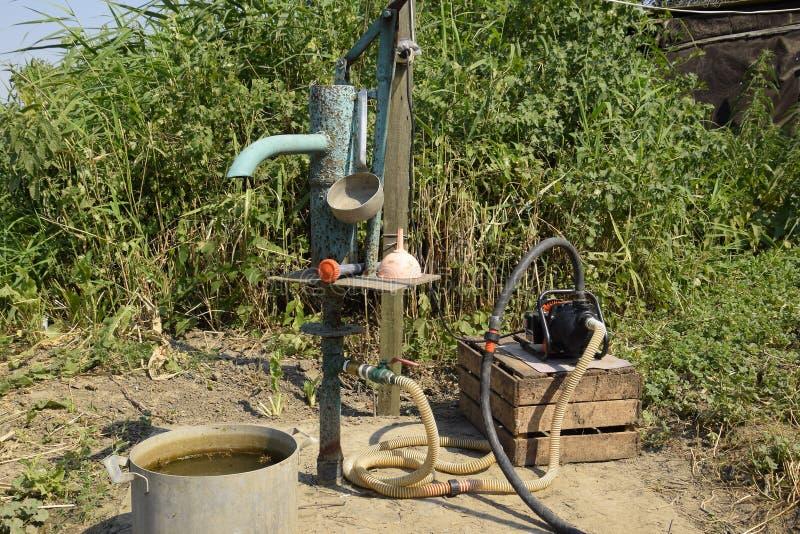 Sistema de irrigação no jardim da casa Bem com manual e a bomba automática fotos de stock