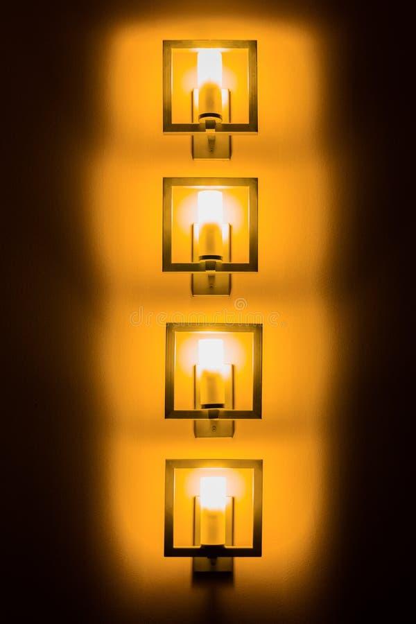 Sistema de lámparas de pared amarillas en la oscuridad fotos de archivo