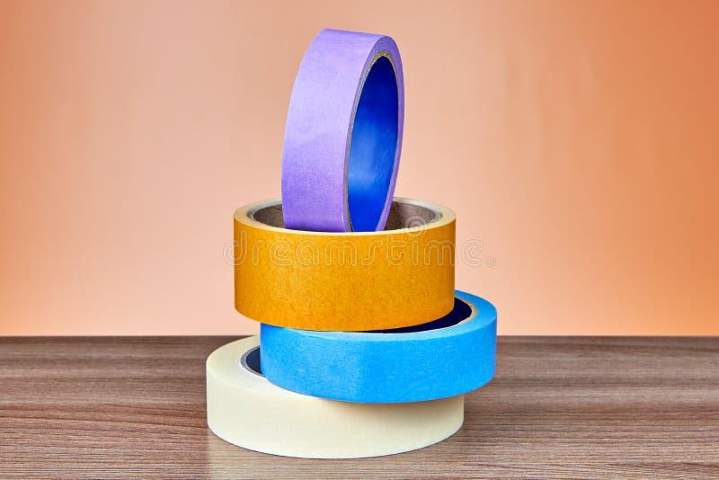 Sistema de la cinta auta-adhesivo multicolora en fondo anaranjado foto de archivo