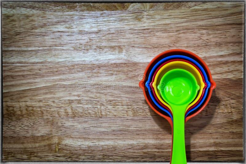 Sistema de la cuchara dosificadora colorida en un fondo de madera fotos de archivo libres de regalías