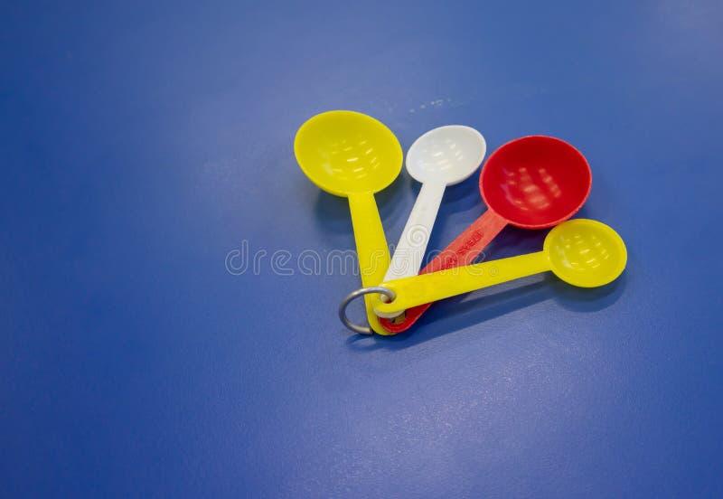 Sistema de la cuchara dosificadora plástica colorida aislada en backgro azul foto de archivo