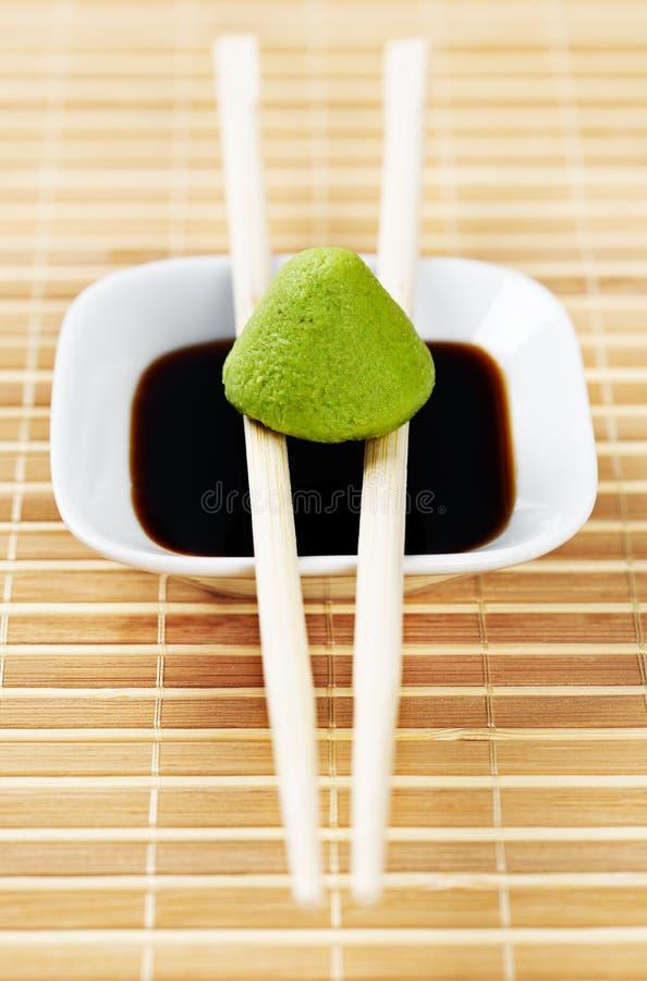 Sistema de la fuente del wasabi y de la soja en un mantel de bambú con los palillos de madera imagen de archivo