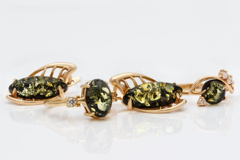 Sistema de la joyería del primer de pendientes y de anillos de oro con el ámbar verde báltico natural auténtico imagenes de archivo