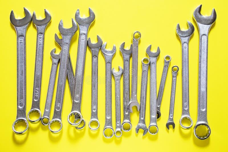 Sistema de la llave inglesa Llaves inglesas coloreadas de plata que mienten de lado a lado en fondo amarillo foto de archivo libre de regalías