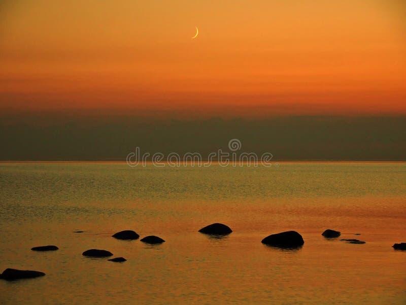 Sistema de la luna y cielo anaranjado sobre costa de la piedra del mar imagen de archivo libre de regalías