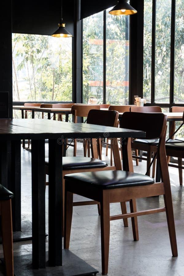 Sistema de la tabla y de la silla en diseño interior minimalistic del café moderno con la ventana grande y las lámparas colgantes foto de archivo