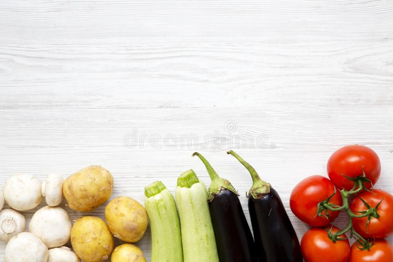 Sistema de las verduras crudas frescas para cocinar la comida vegetal sana en un fondo de madera blanco, visión superior Consumic imagen de archivo