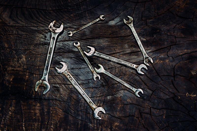 Sistema de llaves inglesas en un fondo de madera oscuro fotografía de archivo