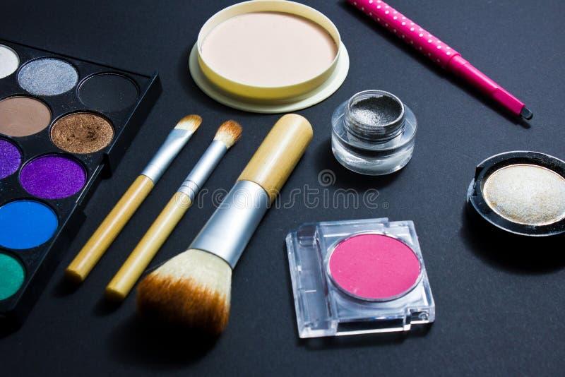 Sistema de los cosméticos profesionales para el maquillaje en fondo negro imagenes de archivo