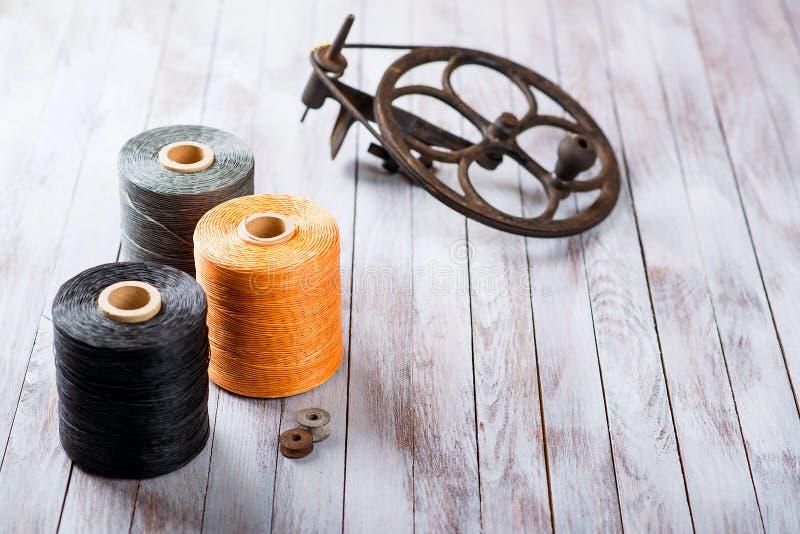 Sistema de los hilos de coser para los zapatos en un fondo de madera foto de archivo