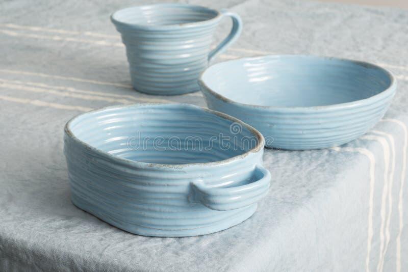 Sistema de loza de barro azul en el lino azul foto de archivo