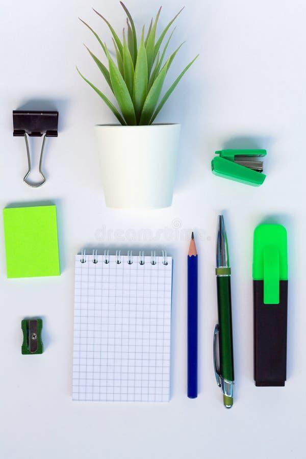 Sistema de objetos de la oficina cuaderno, pluma azul y otros materiales de oficina verdes o negros en una opinión de top blanca  foto de archivo