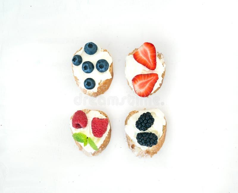 Sistema de pequeños bocadillos dulces con el queso cremoso y el bosque fresco fotos de archivo libres de regalías