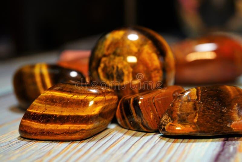Sistema de piedras preciosas minerales naturales de cierto tipo Tiger Eye Semiprecious Gemstone Birthstone en una tabla de madera fotos de archivo libres de regalías