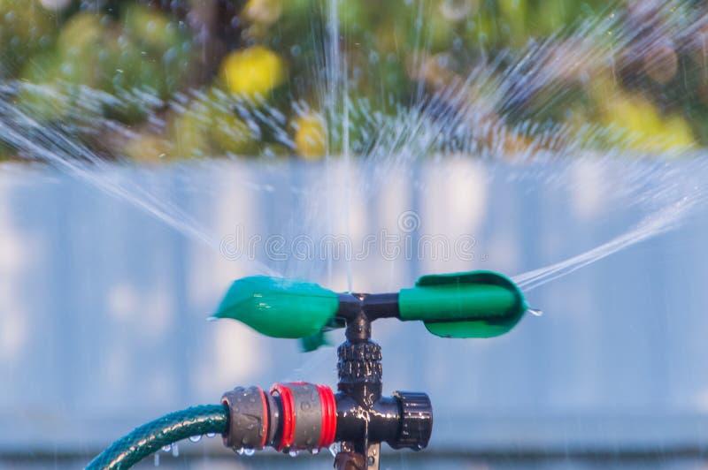 Sistema de riego automático con descensos del agua en el jardín foto de archivo