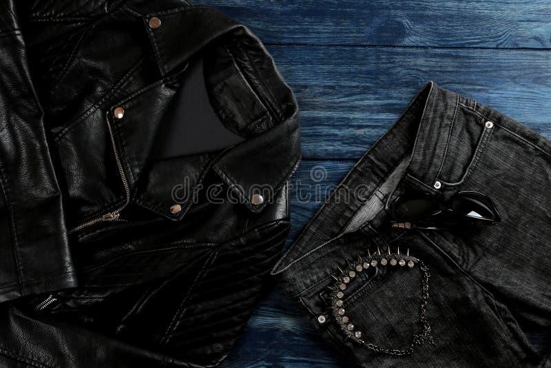 Sistema de ropa elegante del ` s de las mujeres negras, complementos del ` s de las mujeres, estilo negro, en fondo de madera azu foto de archivo