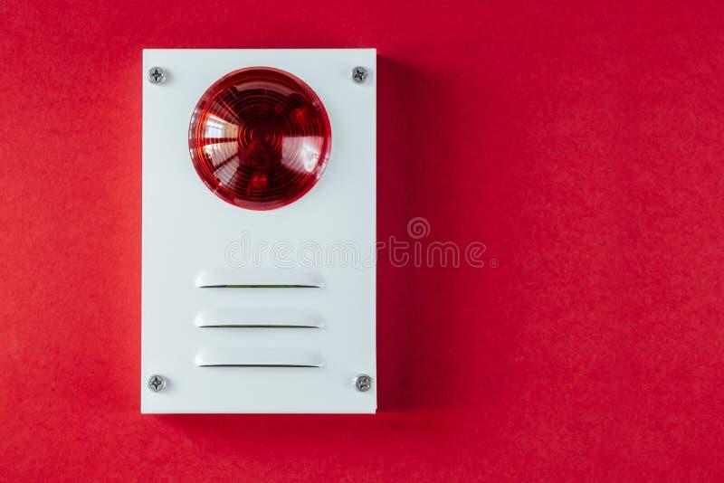 Sistema de seguridad contra incendios en un fondo rojo de un espacio de la copia foto de archivo