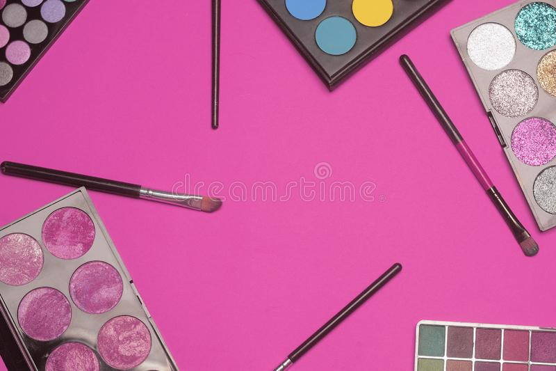 Sistema de sombra de ojos Componga los productos en fondo rosado con el espacio vacío en el centro Cepillos del maquillaje y colo imagen de archivo