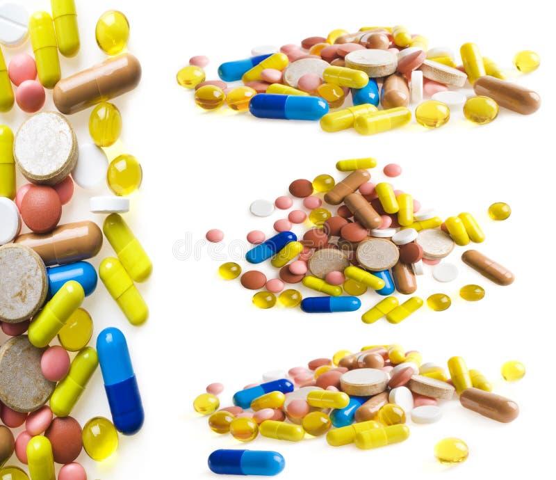 Sistema de tabletas y de cápsulas multicoloras en el fondo blanco imagenes de archivo