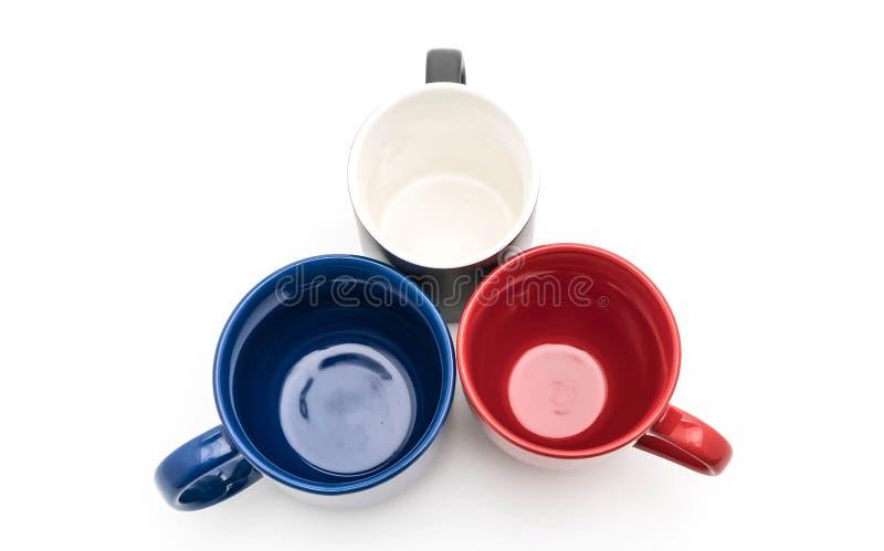 Sistema de tazas negras, rojas y azules en blanco fotografía de archivo
