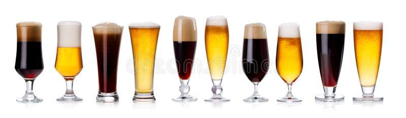 Sistema de tazas y de vidrios con la cerveza ligera y oscura aislada en whi foto de archivo