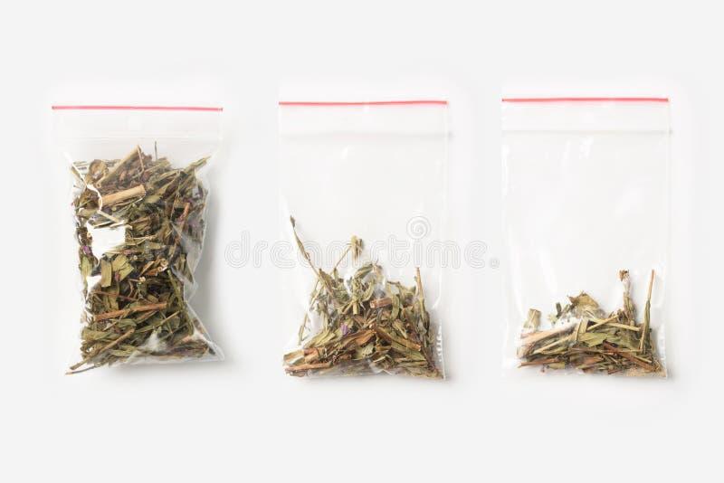 Sistema de tres VACÍOS, MEDIOS Y LLENOS bolsos transparentes plásticos de la cremallera con el té floreciente de Sally aislado en imágenes de archivo libres de regalías