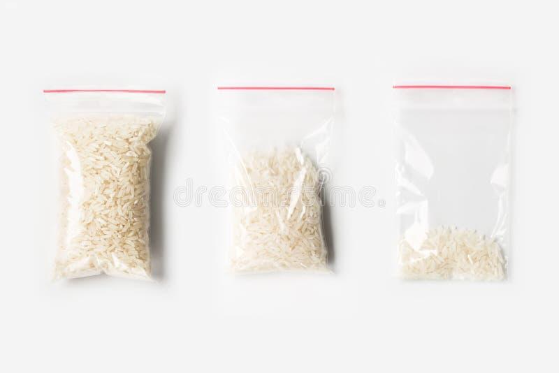 Sistema de tres VACÍOS, MEDIOS Y LLENOS bolsos transparentes plásticos de la cremallera con el arroz basmati blanco crudo aislado fotografía de archivo libre de regalías