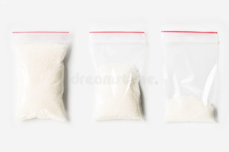 Sistema de tres VACÍOS, MEDIOS Y LLENOS bolsos transparentes plásticos de la cremallera con el azúcar granulado aislado en blanco fotos de archivo