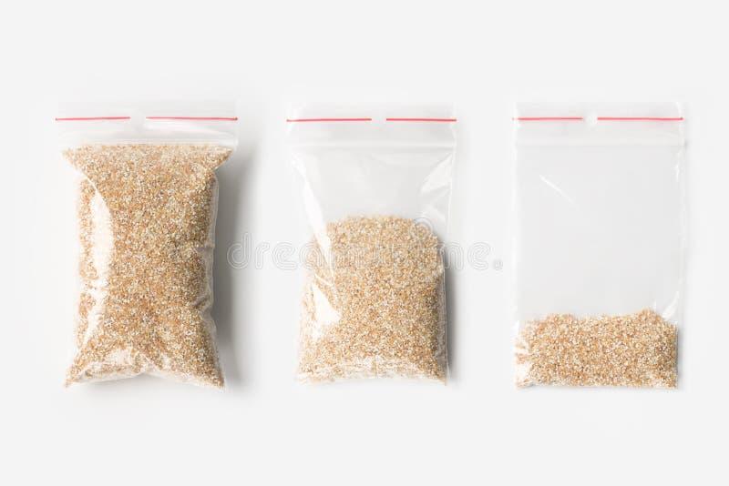 Sistema de tres VACÍOS, MEDIOS Y LLENOS bolsos transparentes plásticos de la cremallera con las arenas crudas del trigo aisladas  imagenes de archivo